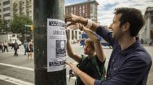Whitney Brown and Andrew O'Sullivan from the Pivot Legal Society hang wanted posters of George Wolsey at Main and Hastings streets in Vancouver September 4, 2013. George Wolsey a landlord who currently owes a total of $18,163.75 to 10 different residents of the Wonder Rooms SRO. (John Lehmann/The Globe and Mail)