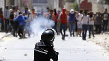 A riot police officer fires teargas during clashes with supporters of Islamist group Ansar al-Sharia in Tunis on May 19, 2013. Supporters of the hardline Islamist group clashed with Tunisian police in two cities after the government banned its annual rally and the regional arm of al-Qaeda urged it to stand firm against the authorities. (ANIS MILI/REUTERS)