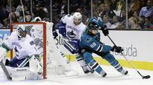 San Jose Sharks' Brent Burns (88) is chased by Vancouver Canucks' Ryan Stanton (18) as goalie Roberto Luongo, left, watches during the first period of an NHL game Thursday, Oct. 3, 2013, in San Jose, Calif. (Marcio Jose Sanchez/AP)