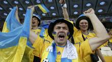 Ukraine's fans wear national colors as they cheer before their Group D Euro 2012 soccer match against Sweden at the Olympic stadium in Kiev, June 11, 2012. (ALEXANDER DEMIANCHUK/REUTERS)