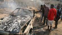 Men look at the wreckage of a car following a bomb blast at St Theresa Catholic Church outside the Nigerian capital Abuja on December 25, 2011. Two explosions near churches during Christmas Day services in Nigeria, including one outside the country's capital, killed at least 25 people amid spiralling violence blamed on an Islamist group. The suspected attacks stoked fear and anger in Africa's most populous nation, which has been hit by scores of bombings and shootings attributed to Islamist group Boko Haram, with authorities seemingly unable to stop them. (-/AFP/Getty Images/-/AFP/Getty Images)