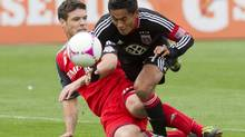 Toronto FC 's Darren O'Dea, left, tackles D.C United's Andy Najar during first half MLS action in Toronto on Saturday, October 6, 2012. (Chris Young/THE CANADIAN PRESS)