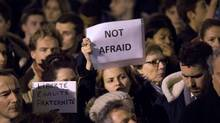 People hold up placards at a vigil outside The French Institute in London on January 9, 2015 for the 12 victims of the attack on the Paris offices of satirical weekly Charlie Hebdo. (Justin Tallis/AFP/Getty Images)