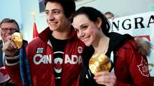 Olympic gold medalists in ice dance Scott Moir and Tessa Virtue pose for photos with their medals as they are welcomed home by fans and family at the airport in London, Ontario. (GEOFF ROBINS/The Canadian Press)