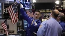 Specialist Joseph Mastrolia, left, works with traders on the floor of the New York Stock Exchange. (Richard Drew/AP)