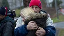 Local residents comfort each other near a makeshift memorial to the victims of the Sandy Hook School shooting in Newtown, Connecticut Sunday, December 16, 2012. (Kevin Van Paassen/The Globe and Mail)