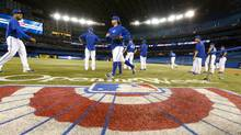 A banner is painted on the field in preparation for the the Toronto Blue Jays home opener as they face the Cleveland Indians at the Rogers Centre on Tuesday. (Fred Lum/The Globe and Mail)