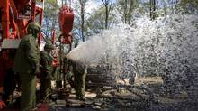 Workers flush out water during a fracking operation at a natural gas well in Pleasant Valley, Pa. The procedure helps release natural gas from the rock layers by cracking the shale and sandstone formations using water and sand under intense pressure, allowing the captured gas to seep out. (Robert Nickelsberg/Robert Nickelsberg/Getty Images)