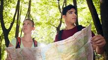 young couple looking at map during trek (diego cervo/Getty Images/iStockphoto)