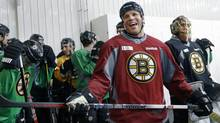 Boston Bruins forward Shawn Thornton laughs with a reporter as he, goaltender Tuukka Rask, far right, and teammates wait to go onto the ice for NHL hockey practice at Ristuccia Arena in Wilmington, Mass., Monday, Jan. 14, 2013. (Associated Press)