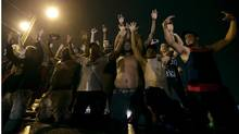 People defy a curfew Aug. 17 before smoke and tear gas was fired to disperse a crowd protesting the shooting of teenager Michael Brown last Saturday in Ferguson, Mo. (Charlie Riedel/AP)
