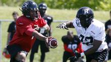 Ottawa Redblacks quarterback Henry Burris hands off the ball to Eric O'Neal at the first day of CFL training camp at Keith Harris Stadium in Ottawa on Sunday, June 1, 2014. (The Canadian Press)