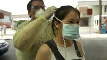 Sars screener Carlo Ordonez helps patient Michelle Duong with her mask at entrance to Toronto Western Hospital in this 2003 file photo. A mathematical study suggests that when public health officials are speaking to reporters about an outbreak, they should include information about the rate at which a disease is spreading and not just the total number of cases in a population. (Fred Lum/The Globe and Mail)