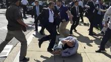 In this frame grab from video provided by Voice of America, members of Turkish President Recep Tayyip Erdogan's security detail are shown violently reacting to peaceful protesters during Erdogan's trip last month to Washington. (Voice of America via AP)