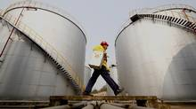 In this 2010 file photo, a worker walks past tanks at an oil storage base in Suining, in southwest China's Sichuan province. (The Associated Press)