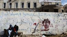 Libyan rebel supporters sit outside rebel headquarters decorated with revolutionary graffiti in the northeastern city of Benghazi, March 23, 2011. (FINBARR O'REILLY/FINBARR O'REILLY/REUTERS)