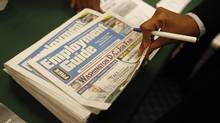 A job seeker picks up a copy of the Washington Job Guide at a job fair in a Washington hotel in this file photo. (JASON REED/REUTERS)