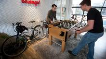 Ryan Betts, left, direct of user experience, and Hubert Florin, a senior designer, play foosball during a break at Bazinga! in Vancouver, B.C., on Wednesday August 13, 2014. The company offers a cloud-based platform for online interaction between residents in condo buildings and property management and developers. (DARRYL DYCK/THE CANADIAN PRESS)