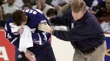 Toronto Maple Leafs Bryan Berard is assisted off the ice by a team trainer following a blow to the face in second period NHL action against the Ottawa Senators at the Corel Centre in Kanata, Ont. Saturday, March 11, 2000. (JONATHAN HAYWARD/CP)