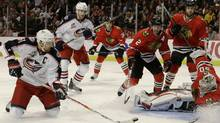 Columbus Blue Jackets left wing Rick Nash, left, takes a shot on goal from his knees at Chicago Blackhawks goalie Corey Crawford, right, during the first period of their NHL hockey game Saturday, Oct. 23, 2010 in Chicago. (Charles Rex Arbogast)