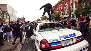 A protestor jumps on an abandonned police car after clashes during a G20 protest in Toronto.