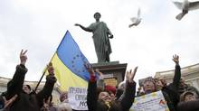 Ukrainian women hold an Ukrainian national flag with EU stars while releasing birds as a symbol of peace after singing of the national anthem during an anti-war protest in front of a monument of Duke de Richelieu in the Black Sea port of Odessa, Ukraine, Sunday, March 9, 2014. The monument to the prominent French statesman de Richelieu, in background, marks the respect he is accorded in the area after he was appointed to office by Russian Czar Alexander I in 1803 to rule as governor in the New Russian region including Odessa. (Sergei Poliakov/AP)