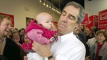 Liberal leader Michael Ignatieff picks up 4-month-old Maeby Robertson, as he attends a rally at the campaign office in Kitchener Centre Friday, April 1, 2011 on a campaign stop in Kitchener, Ont. (Ryan Remiorz/The Canadian Press/Ryan Remiorz/The Canadian Press)