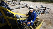 An oil field worker walks up a flight of stairs near wellheads that inject steam into the ground and pump oil out at the Cenovus Energy Christina Lake Steam-Assisted Gravity Drainage (SAGD) project near Fort McMurray, Alta., in this file photo. (© Todd Korol / Reuters)