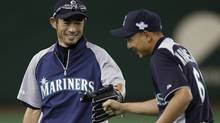 Seattle Mariners' Ichiro Suzuki and Munenori Kawasaki smile during a workout session for their American League season opening MLB baseball game against the Oakland Athletics in Tokyo. (Toru Hanai/Reuters)