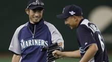 Seattle Mariners' Ichiro Suzuki and Munenori Kawasaki smile during a workout session for their American League season opening MLB baseball game against the Oakland Athletics in Tokyo. (Toru Hanai/Reuters)