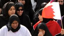 "Anti-government protesters carry Bahraini flags during a march of thousands Tuesday, March 15, 2011, to the Saudi embassy in Manama, Bahrain. Some of the women wore white burial shrouds, signifying a willingness to die, and the one at center reads ""I am the next martyr."" Bahrain's king declared a three-month state of emergency Tuesday to quell a Shiite uprising, as clashes spread through the capital and surrounding villages in a showdown that drew in the region's major powers and splintered along its main sectarian faultlines. At least two Bahrainis and a Saudi soldier died, and hundreds of protesters were injured by shotgun blasts and clubs. (AP Photo/Hasan Jamali) (Hasan Jamali/AP)"