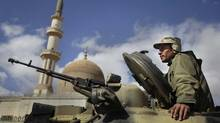 A pro-Gadhafi Libyan soldier sits in an armoured vehicle next to a mosque in Qasr Banashir, southeast of the capital Tripoli, in Libya, Tuesday, March 1, 2011. (Ben Curtis/Ben Curtis/AP)