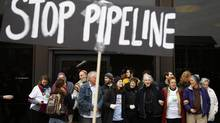 Protesters demonstrating against the proposed Keystone XL oil pipeline block the door to the federal building in Philadelphia on March 10, 2014. (MATT ROURKE/ASSOCIATED PRESS)