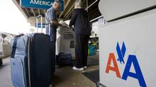 People check luggage outside the American Airlines terminal at Philadelphia International Airport. (Matt Rourke/The Associated Press)