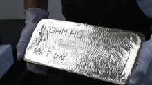 A worker carries a finished silver bar. (PETER ANDREWS/Reuters)