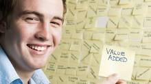 Smiling young man holds note saying VALUE ADDED (Don Bayley/Getty Images/iStockphoto)