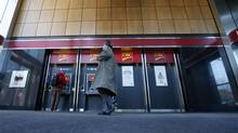 Pedestrians use the CIBC ATM machines in Montreal, April 24, 2014. (CHRISTINNE MUSCHI/REUTERS)