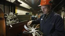 Rob McBain, president and CEO of Ancast Industries Ltd., a Winnipeg firm that makes custom castings used in auto, tractor and forklift sectors, is photographed looking at finished tractor parts in his Winnipeg plant Friday, January 10, 2014. (John Woods for The Globe and Mail)