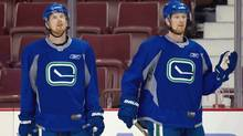 Vancouver Canucks' Daniel Sedin, left, and his twin brother Henrik Sedin, both of Sweden, look on during team practice in Vancouver, B.C., on Saturday May 14, 2011. (The Canadian Press)