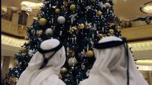 Two Emirate men look to a Christmas tree which has been decked out with dollars 11 million U.S. (14.3 million euro) worth of gold, at the Emirates Palace hotel, in Abu Dhabi, United Arab Emirates, on Thursday Dec. 16, 2010. The hotel's general manager, Hans Olbertz, was quoted in local newspapers Thursday as saying the 43-foot (13-meter) faux fir has 131 ornaments that include gold and precious stones including diamonds and sapphires. The $11 million symbol of the season has become the latest extravagance at the Emirates Palace hotel, which boasts its own marina, heliport and a vending machine that pops out small gold bars. (Hussein Malla/(AP Photo/Hussein Malla))