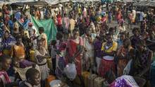 People wait to fill<137,2014/07/09,pmremote11> up<137> water containers in Bentiu, South Sudan, on July 2. World Vision warns that famine in the country is 'almost certain.' (Matthew Abbott/AP)