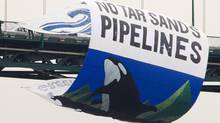 Greenpeace activists hang a large banner off the Lions Gate bridge in Vancouver, B.C. Tuesday, May 29, 2012. The banner is to protest the tar sands and the expansion of the oil pipelines. (Jonathan Hayward/The Canadian Press/Jonathan Hayward/The Canadian Press)