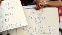 """People show banners reading """"hands off from poors"""" outside Italy's Parliament on Aug.11, 2011, ahead of Finance Minister Giulio Tremonti's address. Italy outlined plans for """"very strong"""" budget cuts next year including an increase in taxes on investment accounts and cuts in social welfare. (VINCENZO PINTO/AFP/Getty Images)"""