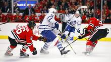 Chicago Blackhawks left wing Teuvo Teravainen (86) loses his stick as Toronto Maple Leafs defenseman Jake Gardiner (51) and Blackhawks defenseman Michal Rozsival (32) battle for the puck during the first period of an NHL hockey game on Monday, Feb. 15, 2016, in Chicago. (Jeff Haynes/AP)