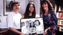 Jackie Lynn and Sue at 35 in 1992 holding a photograph of themselves at 28, 21 and 7.