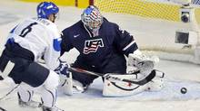 Team USA goalie John Gibson makes a save on Finland's Teemu Pulkkinen (L) during the second period of play at the 2012 IIHF U20 World Junior Hockey Championship in Edmonton, Alberta, December 28, 2011. (DAN RIEDLHUBER/REUTERS)