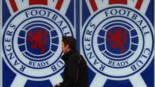 A man walks past a Rangers' soccer club poster at their Ibrox Stadium in Glasgow, Scotland December 19, 2012. Rangers Football Club, which has raised 22 million pounds ($36 million) in a stock market listing, said talk of a European soccer league made it a good investment despite its demotion to Scotland's fourth tier. (DAVID MOIR/REUTERS)