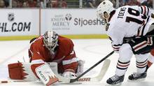 Red Wings goalie Jimmy Howard stops a first-period shot by Jonathan Toews of the Chicago Blackhawks in Detroit on Monday night. Detroit won 3-1. (Paul Sancya/AP)