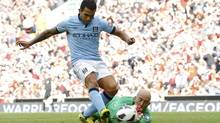 Manchester City's Carlos Tevez (L) scores against Liverpool's keeper Pepe Reina during their English Premier League soccer match at Anfield in Liverpool, northern England, August 26, 2012. (PHIL NOBLE/REUTERS)