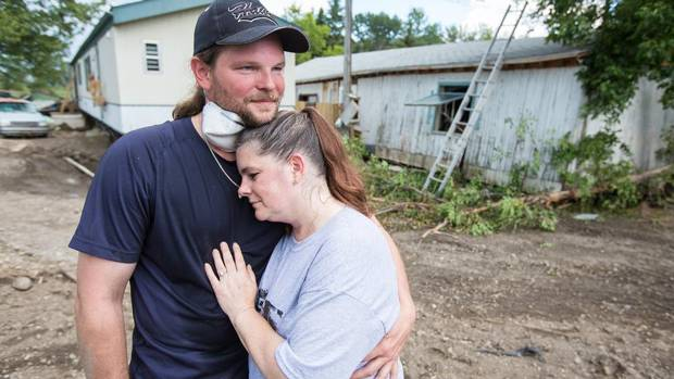 """Floodwaters rose so high, so fast, that Ronda Kalman had to be rescued by boat from her trailer's rooftop. The 43-year-old and her partner, John Willis, 37, returned on Tuesday. But what's left of their home is split down the middle, a crack separating the trailer from its wooden addition. Inside, a deep freezer with rotting deer meat and other game blocks the door, making windows the only way to get at piles of their stuff – just what, it is hard to say – caked in mud. Thirty freshwater fish that were left in their six-foot tank are dead, although the couple's pet snakes survived. Mr. Willis also hands Ms. Kalman an untouched bottle of wine through a broken window. """"It's homemade,"""" she says. """"It is very good."""" When a grinning Mr. Willis walks out of the ruins with another item, a tiny, muddy box, Ms. Kalman trembles and sniffles but manages not to cry. She wipes away gunk to expose an inscription: """"J.R.B. to M.B.B. Jan 1. 1929."""" Her grandfather proposed to her grandmother with a ring from this sterling silver box. (Ronda was wearing the same ring when the disaster hit). For all the ruin, she wants to stay here. """"I like the people. I like the town,"""" she says. (Chris Bolin For The Globe and Mail)"""